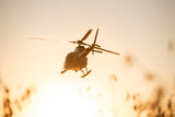 Fototapety Passanger Helicopter flying in sunset sky