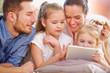 Familie und Kinder spielen mit Tablet PC