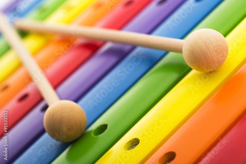 Fototapeta Rainbow colored wooden toy xylophone texture against white backg