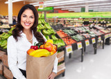 Woman with grocery bag of vegetables.