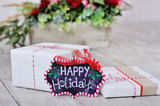 Still life with Happy Holidays sign, wrapped present boxes and flowers on background