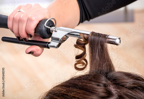 obraz lub plakat Hairstylist using a curling iron or tongs