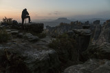 Photographer stands on the edge of the cliff, waiting for sunrise in Saxon Switzerland in autumn