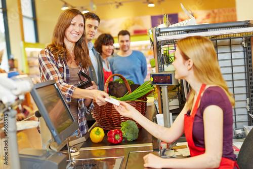 Frau bezahlt bei Kassiererin im Supermarkt