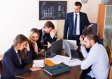 Manager shouting to employees at group meeting