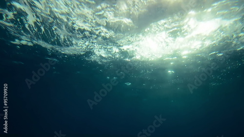 Fotobehang Koraalriffen Beautiful underwater sea scene view with natural light rays in slow motion, shining through the water's glittering and moving surface, caustics, bubbles, and foam, perfect and digital composition