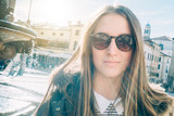 Smiling girl with sunglasses walking in the city
