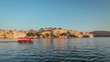 Tourist boat passing in front of Udaipur City Palace, view  from Lake Pichola on sunset. Udaipur, India