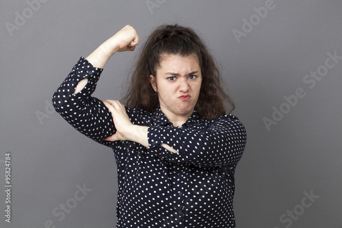 girl power concept - pouting big young brunette showing her muscular arm for fem Poster