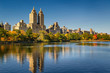 Central Park and Manhattan, Upper West Side with colorful Fall foliage. A clear blue sky and buildings of Central Park West reflecting in the Jacqueline Kennedy Onassis Reservoir. New York City.