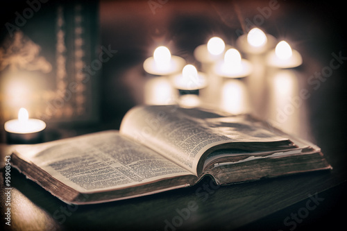 Poster Bible with candles in the background.