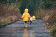 Girl with teddy bear in matching yellow raincoats walking in the