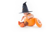Little boy in a pumpkin in witch hat reaching for candy