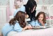 Obrazy na płótnie, fototapety, zdjęcia, fotoobrazy drukowane : Мама с дочками читают сказки на кровати в одинаковой одежде