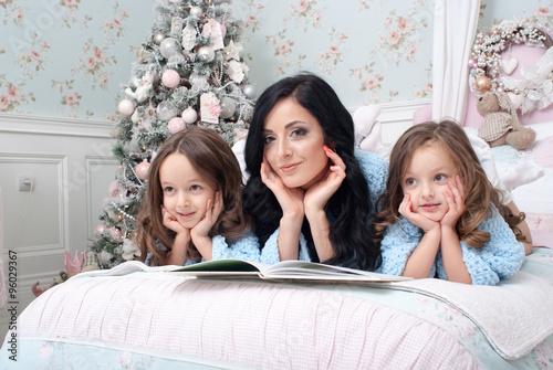 Zdjęcia na płótnie, fototapety, obrazy : Молодая женщина с дочерьми на кровате читают сказки и мечтают