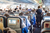 Interior of airplane with passengers on seats.