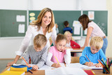 freundliche lehrerin mit kindern in der grundschule - 96066374