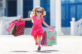 Fototapety Little girl with shopping bags goes to the store