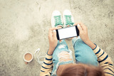 Fototapety woman holding phone white screen on top view vintage style