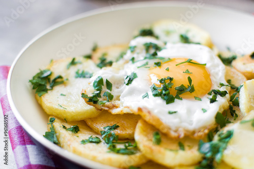 Foto: Potatoes, fried eggs and parsley in a frying pan