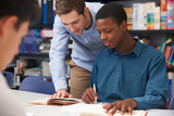 Fototapety Teacher Helping Male Student In Classroom