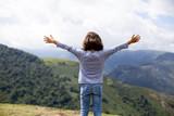 Niña con los brazos abiertos frente a la montaña