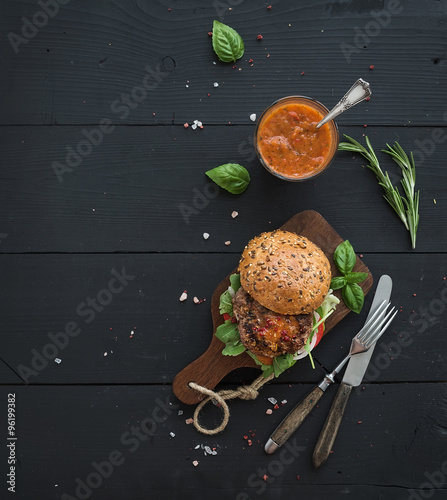 Fresh homemade burger on dark serving board with spicy tomato sauce, sea salt and herbs over black wooden background. Top view