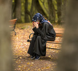 depressed muslim female sitting on the bench