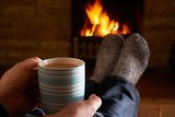 Man With Hot Drink Relaxing By Fire