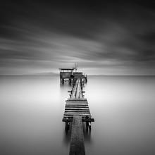 Fine art beeld van houten visserij pier bij het strand in zwart en white.Long belichtingsstapgebieden met motion blur.