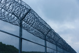 Security fence with a barbed wire with grey sky