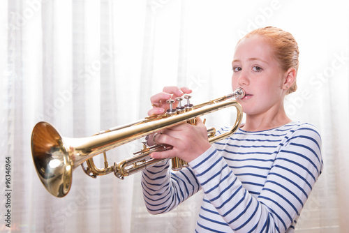 Poster red haired teenage girl playing the trumpet