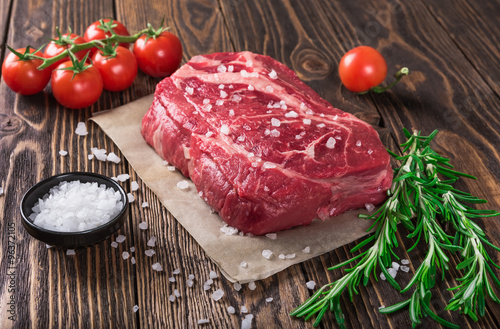 Raw marbled meat steak Ribeye on dark wooden background Poster