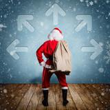 Weihnachtsmann steht vor Wand mit Pfeilen in viele Richtungen