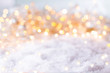 Abstract winter background with snow and golden lights