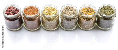 Dried herbal tea of Japanese green tea, lavender, chamomile, linden flower, hibiscus in mason jars over wooden background