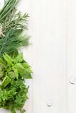 Fresh garden herbs on wooden table - 96450730