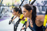 Fototapety Fitness trx suspension straps training exercises women doing push-ups, working with own weith at gym