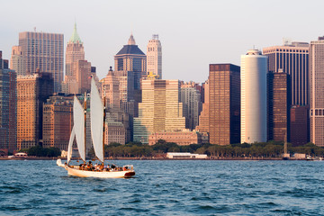 The lower Manhattan skyline in New York with a sailboat