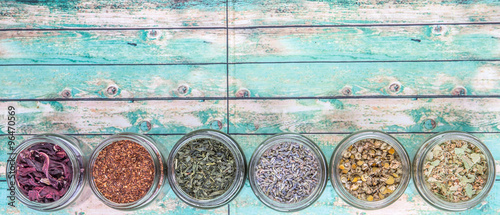 Dried herbal tea lavender, chamomile, linden flower, hibiscus, rooibos, Japanese green tea in mason jar over wooden background