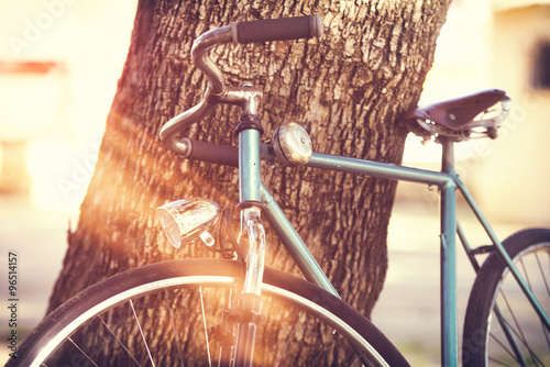 fototapeta na ścianę Old bicycle leaning against a tree