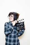 Smiling teen woman with clapper board