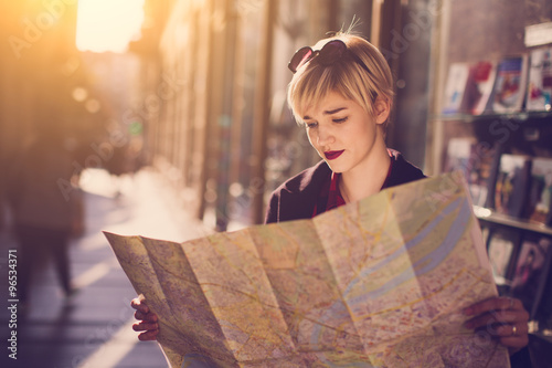 fototapeta na ścianę Young beautiful female traveler standing on the street and looking at the map