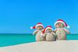 Family of Snowmen in santa hats at tropical beach. Christmas con