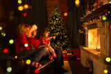 Happy family sitting by fire place at Christmas tree.