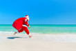 Santa Claus running along beach with sack full of gifts