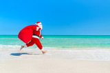Santa Claus running along beach with sack full of gifts - Fine Art prints