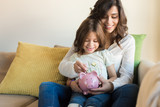 Mom and daughter saving money - 96628731