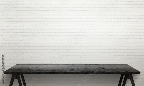 Foto op Canvas Baksteen muur Black wooden table with legs. White brick wall texture in background.