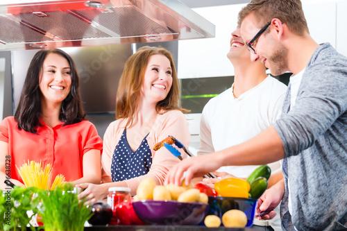 Freunde kochen Spagetti und Fleisch zuhause in Küche